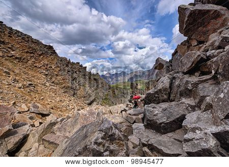 Mountain Tourism. Woman Overcomes Part Of The Way To Large Boulders