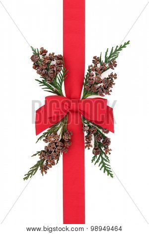 Gift box wrapping with red ribbon with  bow and cedar cypress greenery with pine cones over white background.