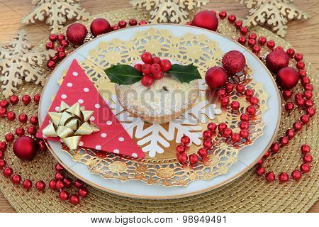 Mince pie and holly with christmas bauble and snowflake decorations over gold background.