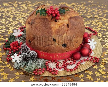 Panettone christams cake with holly, decorations and winter greenery over oak background with gold stars.