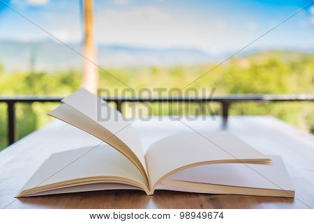 Open book on wood table in green forest ( moving page )