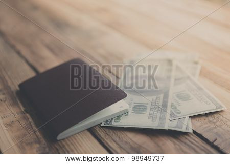 Blank passport with US dollars on wood table ( Filtered image processed vintage effect. )