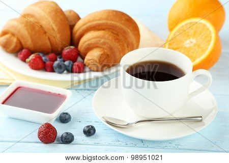Fresh Tasty Croissants With Berries And Coffee On Blue Wooden Background