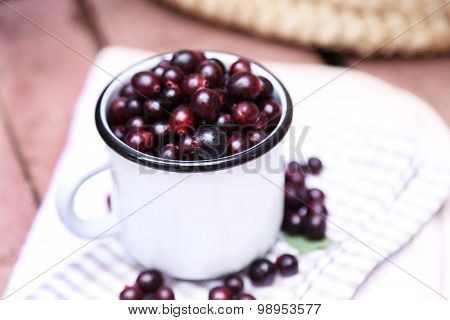 Red gooseberry in cup on wooden table close-up outdoors