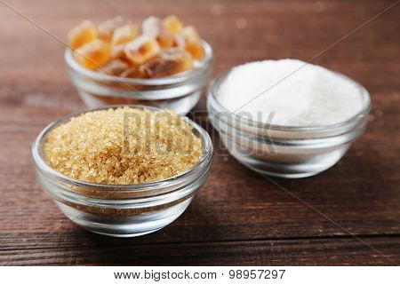 Various Kinds Of Sugar In Bowl On Brown Wooden Background