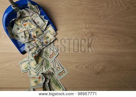 Dollars in garbage scoop on wooden floor background