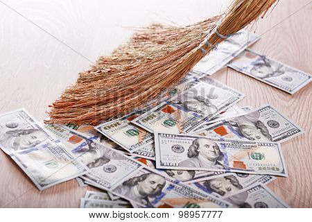 Dollars and broom on wooden floor, closeup