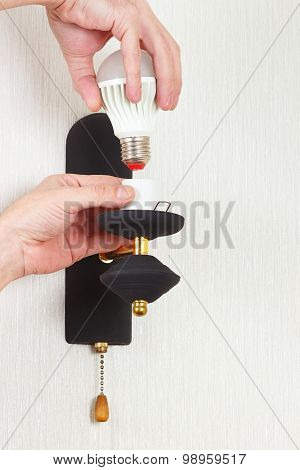 Hand unscrews led bulb in luminaire on white wall