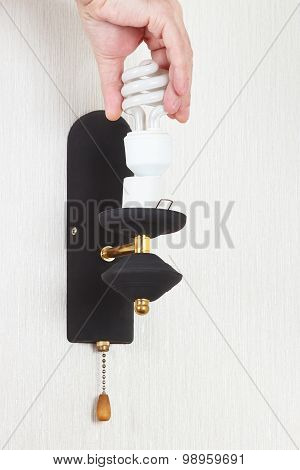 Hand twists tungsten bulb in luminaire on white wall