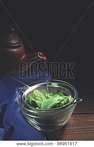 Making mint ice-cream. Pouring hot water through sieve with mint leaves into glass bowl