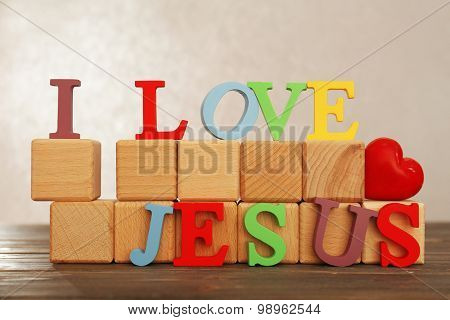 I LOVE JESUS sign illustrated with colorful plastic letters on wooden table on light textured background