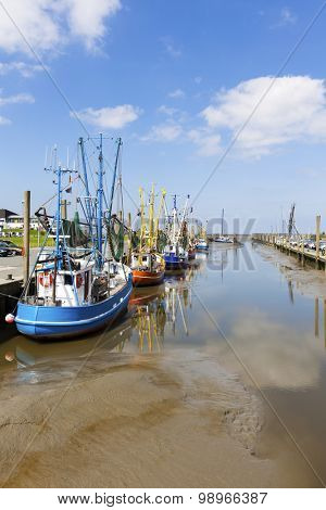 Fishing boats at the harbor of Dorum on the wadden sea coast at low tide