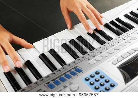 Woman playing synthesizer close up