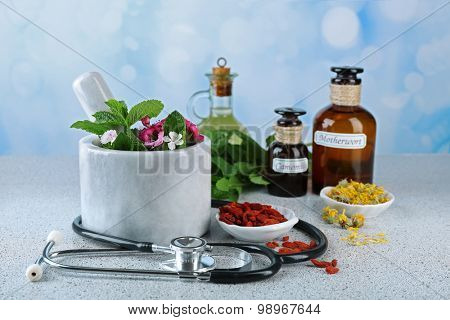 Alternative medicine herbs and stethoscope on wooden table, on light background