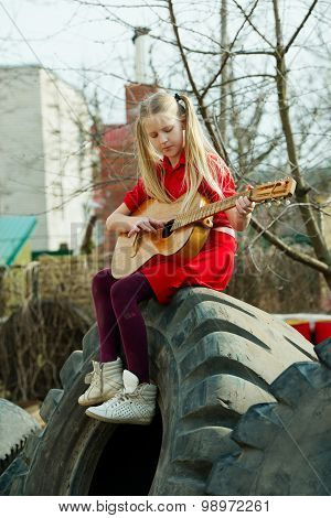 girl playing guitar sitting on tires