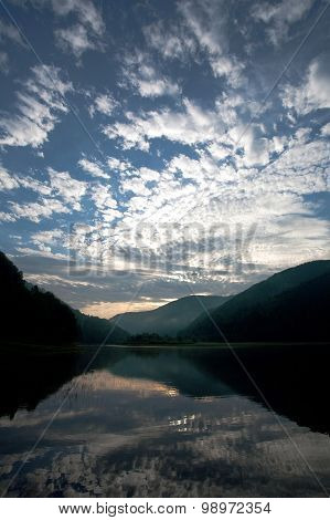Lake In The Mountains In Reflection Of The Dawn Sky And White Clouds