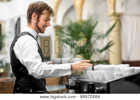 Waiter serving coffee cups