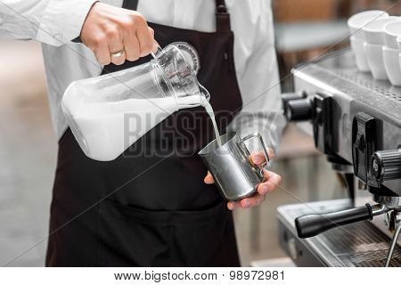 Barista pouring milk to the metal pitcher