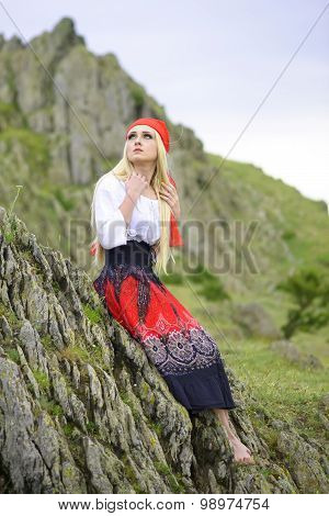 Beautiful Blonde Woman In Old-fashioned Dress Sitting On A Rock