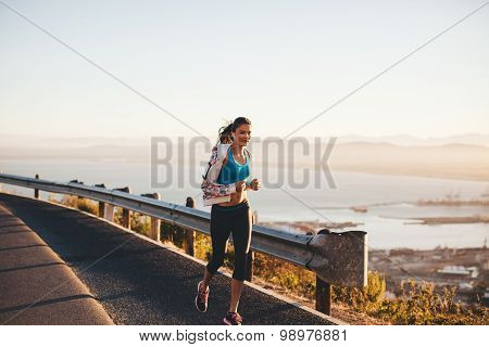 Woman Jogging In Morning On Country Road