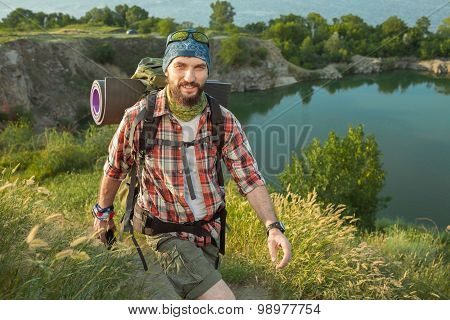 Young caucasian man with backpack walking on the top of hill