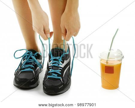 Sportswoman and cup of orange juice, isolated on white