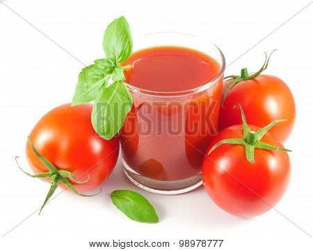 Glass of tomato juice with tomatoes and basil leaves