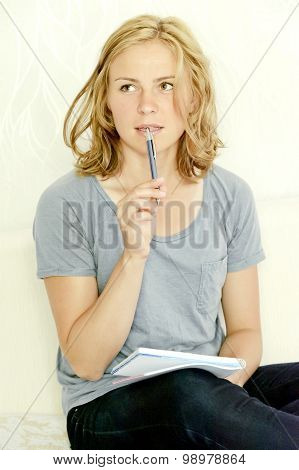 Young woman thinking over making notes in notebook
