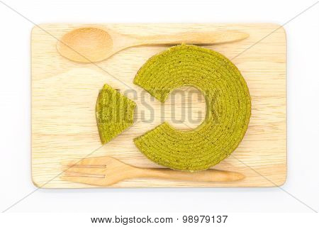 Green tea layer roll cake on wooden board