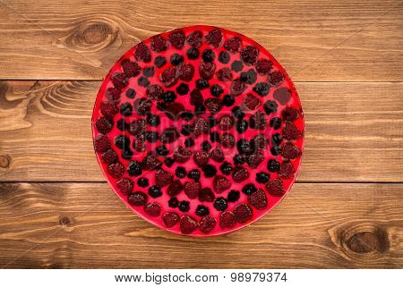 Cheesecake with jelly and berries on the wooden background.