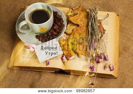 The Cup Of Coffee Lying Ot The Book With Maple Leaves