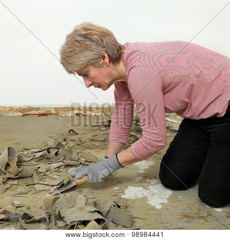 Female Worker Using Putty Knife For Cleaning Floor