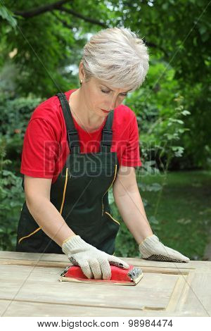 Female Worker Restoring Old Wooden Door