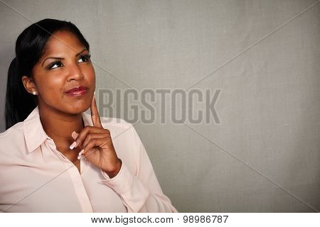 Young Woman Looking Away With A Thinking Gesture