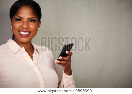 Young Female Holding A Cellphone While Smiling
