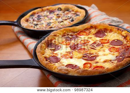 Two cast iron skillet pizzas