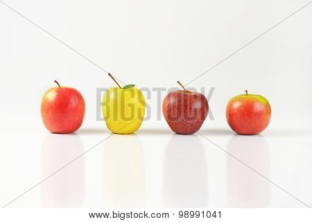 four ripe apples in a row on white background