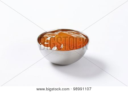 bowl of apricot jam on white background