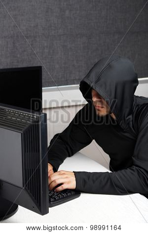 Hacker with computers in room