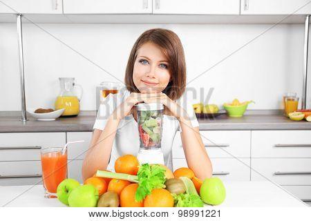 Young beautiful woman using blender, preparing orange juice