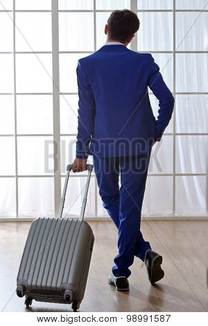 Business man with suitcase in hall