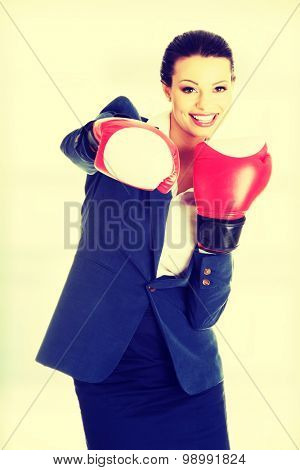 Beautiful young business woman wearing boxing gloves.
