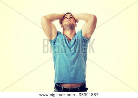 Handsome depressed man with hands behind head.