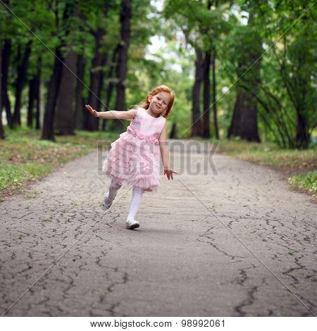 Happy little girl runs in a summer park