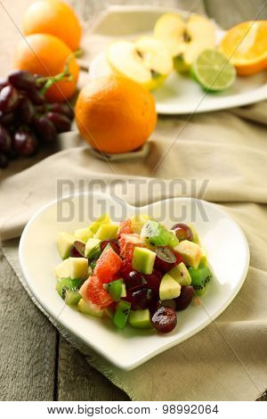 Fruit salad on plate, on wooden background