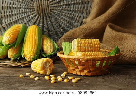 Fresh corn on cobs in wicker bowl on wooden table with sackcloth, closeup