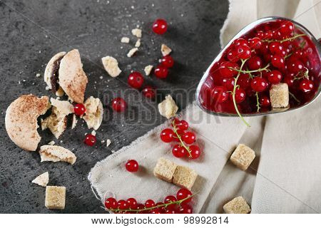 Ripe red currants with lamp sugar on table with sackcloth, top view