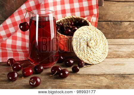 Glass of cherry juice on wooden table with checkered napkin on background