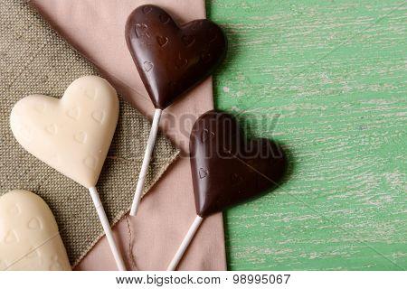 Chocolate heart shaped candies on sticks on sackcloth, closeup