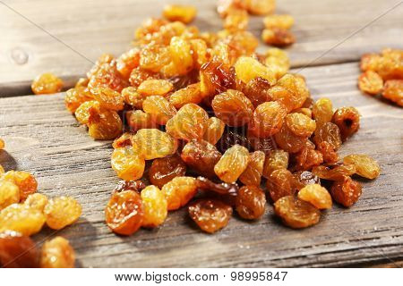 Pile of raisins on wooden table, closeup
